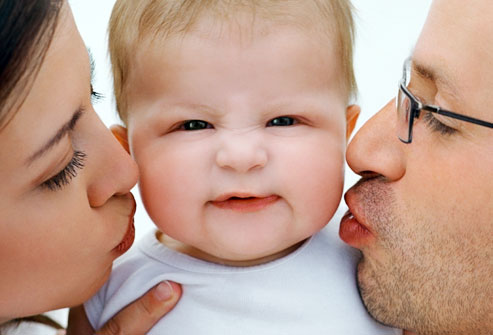 getty_rf_photo_of_parents_kissing_infant